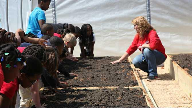 Shanna-Powell-special-education-teacher-and-STEM-committee-member-instructs-second-graders-to-feel-the-soil-heated-in-the-hoop-house-2