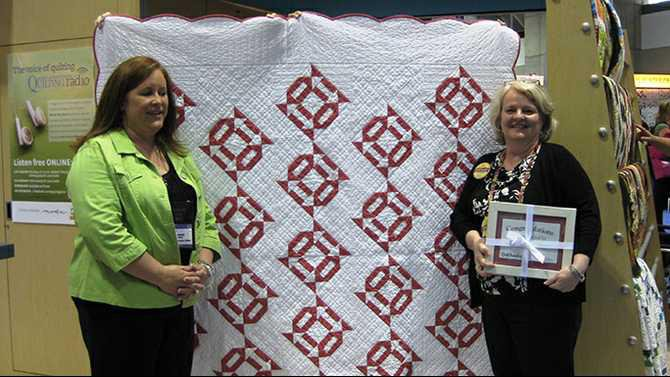 Quilt-story---Melisa-Morrison-right-stands-in-front-of-the-winning-quilt-design-Eye-Candy-and-accepts-the-award-from-Executive-Editor-of-Quilt-Sampler-magazine-Jennifer-Keltner